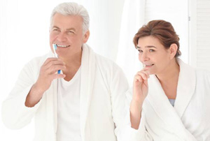 Senior man and woman brushing teeth together