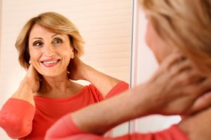 Senior woman in front of mirror admiring her smile