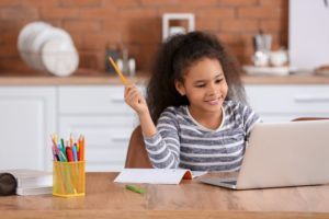 child sitting in front of a laptop doing virtual schooling