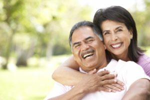 Smiling couple with dental implants in San Antonio