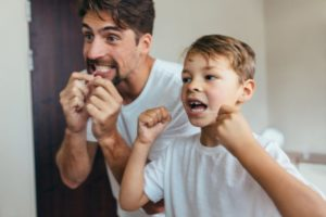 Father and son flossing as recommended by San Antonio pediatric dentist