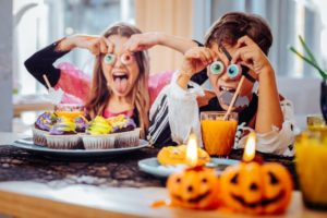 children having fun during Halloween and eating candy