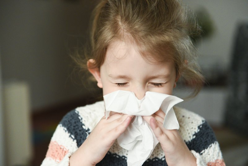 Closeup of child blowing her nose into tissue