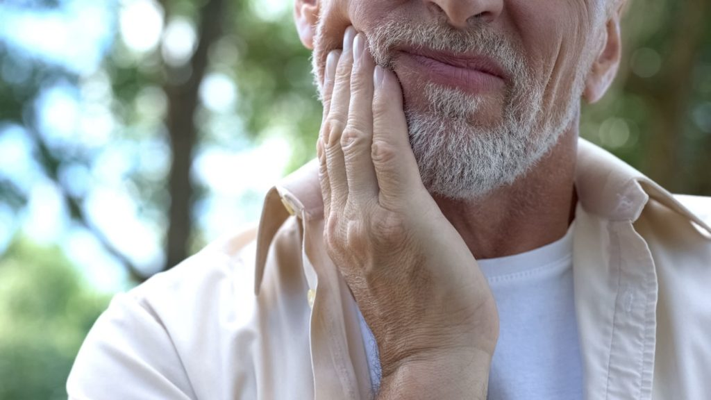 Closeup of senior man experiencing tooth pain