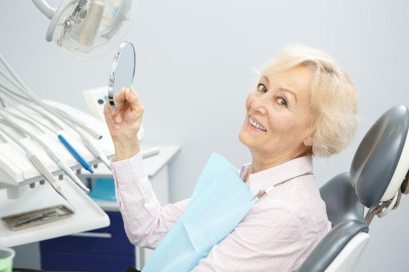 Older woman with dentures leaning back in dental chair