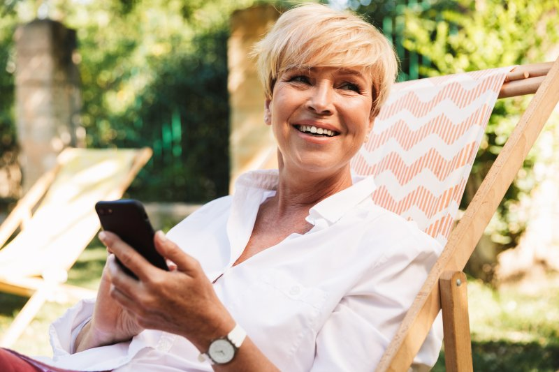 an older woman lounges in a chair in her yard while on her phone and smiling after receiving dental implants in San Antonio