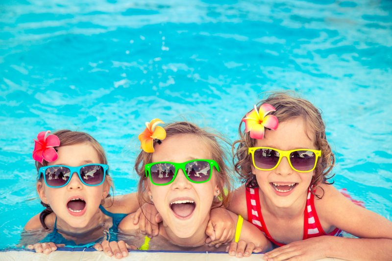 three kids in the pool during the summer